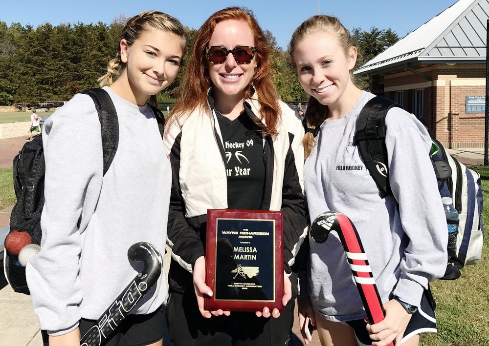 COACH mELISSA mARTIN RECEIVING THE WAYNE RICHARDSON AWARD FOR HELPING GROW FIELD HOCKEY IN NORTH CAROLINA, ALONGSIDE PLAYERS SKYLAR HOLDEN-BACHE AND CLAIRE AFT AT THE 2016 NORTH CAROLINE FIELD HOCKEY STATE CHAMPIONSHIP GAME.