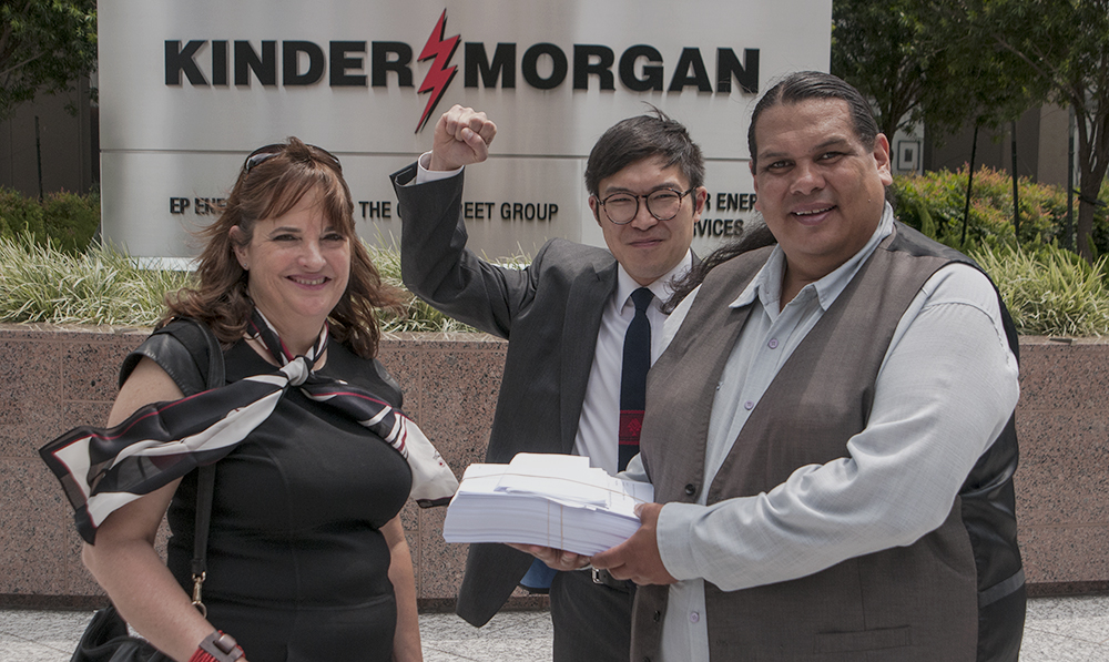 Staff Counsel Eugene Kung, spokesperson Reuben George of Tsleil-Waututh Nation, and a representative from SumOfUs deliver a petition of 60,000 signatures to Kinder Morgan at the oil giant's AGM in Texas, 2015.