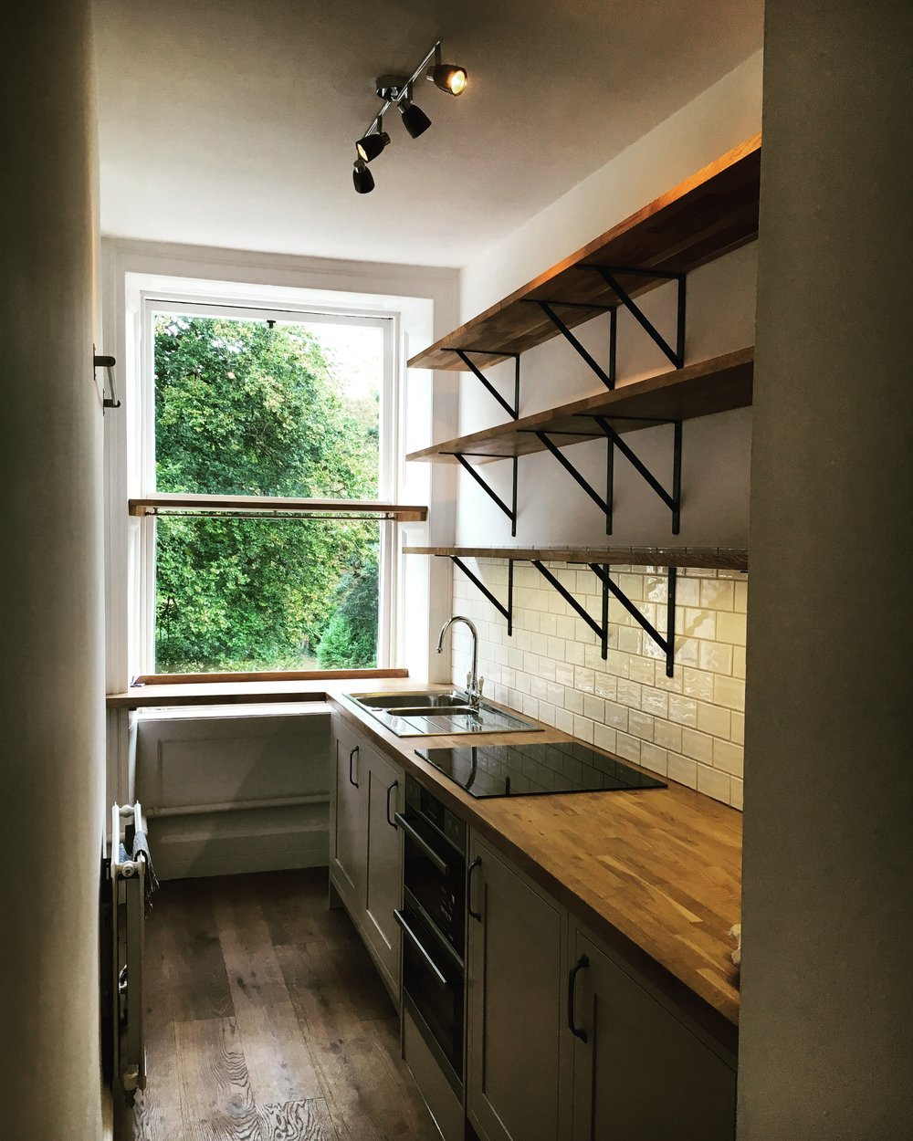 After: A fitted kitchen with integrated appliances, open shelving and new wooden flooring was part of the major renovation of this two bedroom Georgian apartment in the centre of Bath.