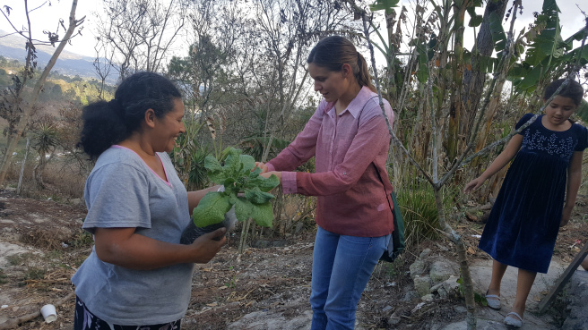 Adria Gamez helping a woman in her vegetable garden