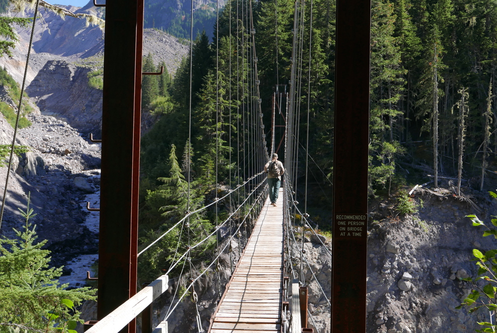 hiker on the Tahoma Creek suspension bridge