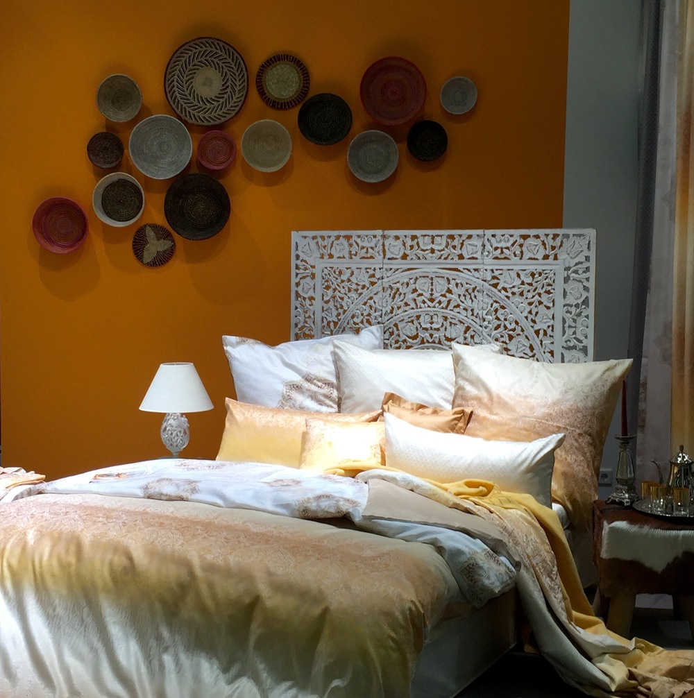 Cool cluster of baskets on the wall. And that wall colour! And the yummy bed.