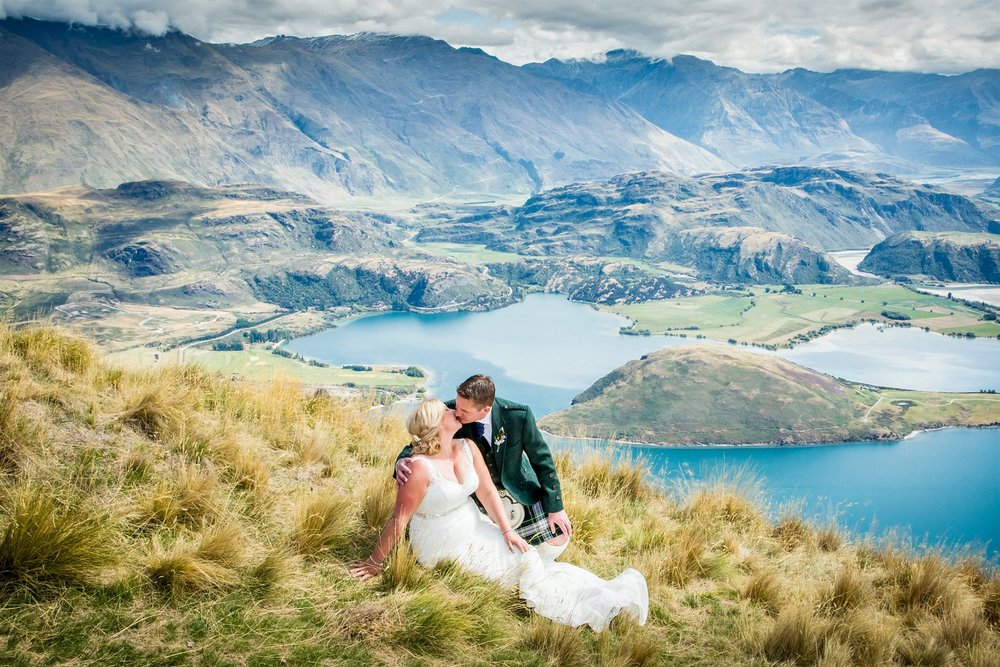 Couple kisses with Lake Wanaka in background
