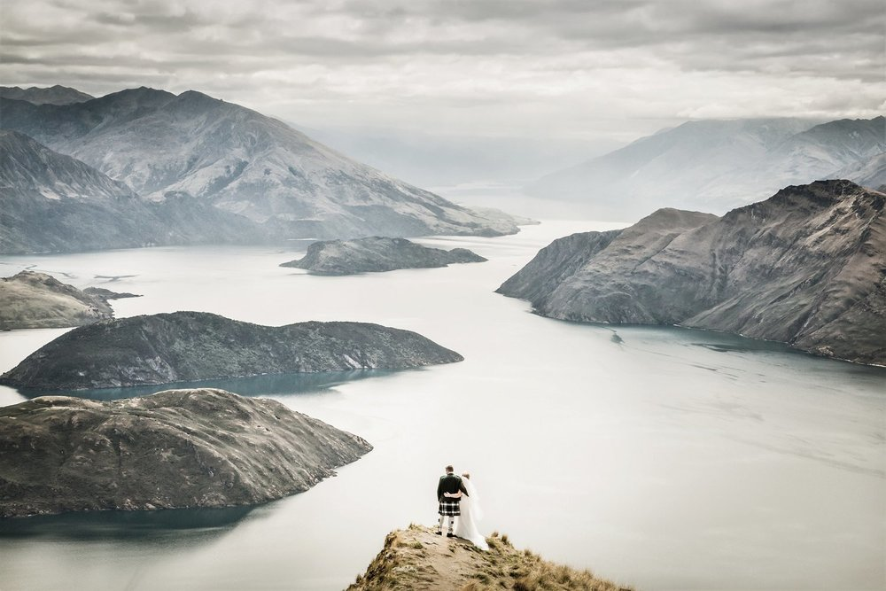 Newlyweds look at Wanaka Lake from Coromandel Peak in New Zealand