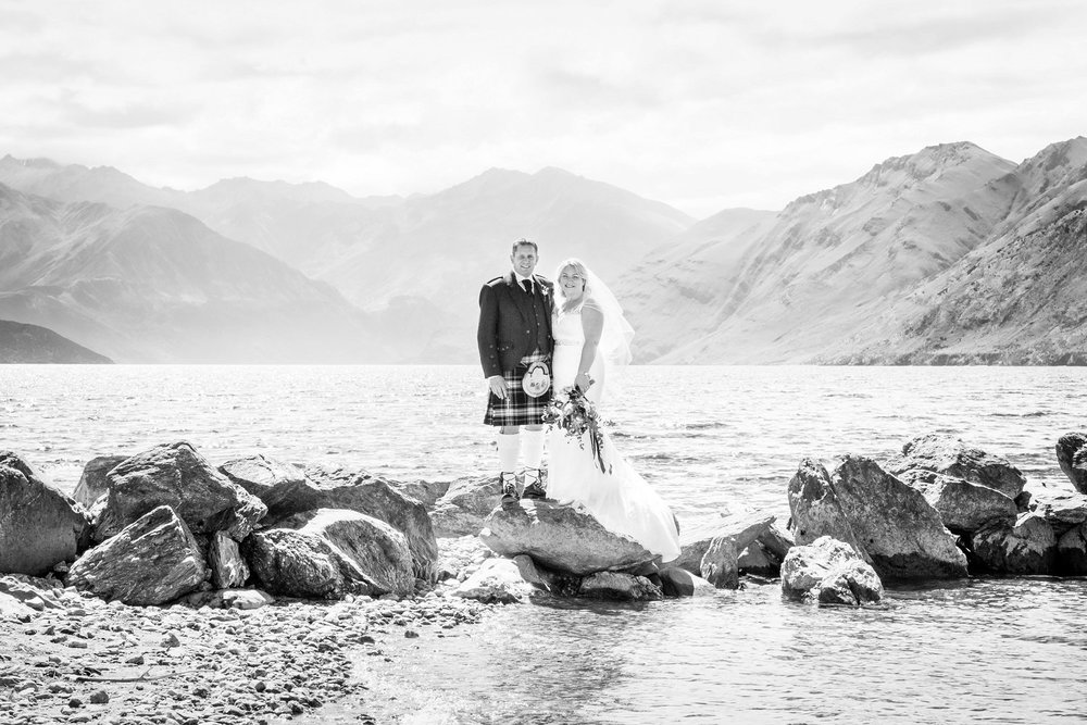 Couple stands on rocks on the Southside if Lake Wanaka