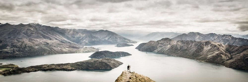 Panoramic picture of newlyweds looking at Wanaka Lake from Coromandel Peak in New Zealand