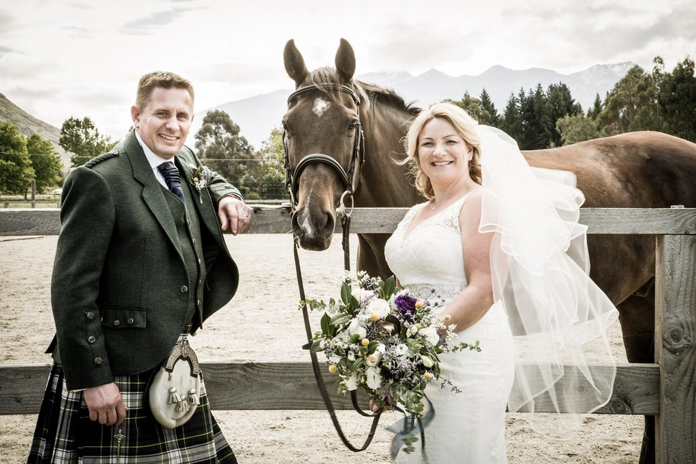 Bride and groom stand with horse at Waterfall Equestrian Centre