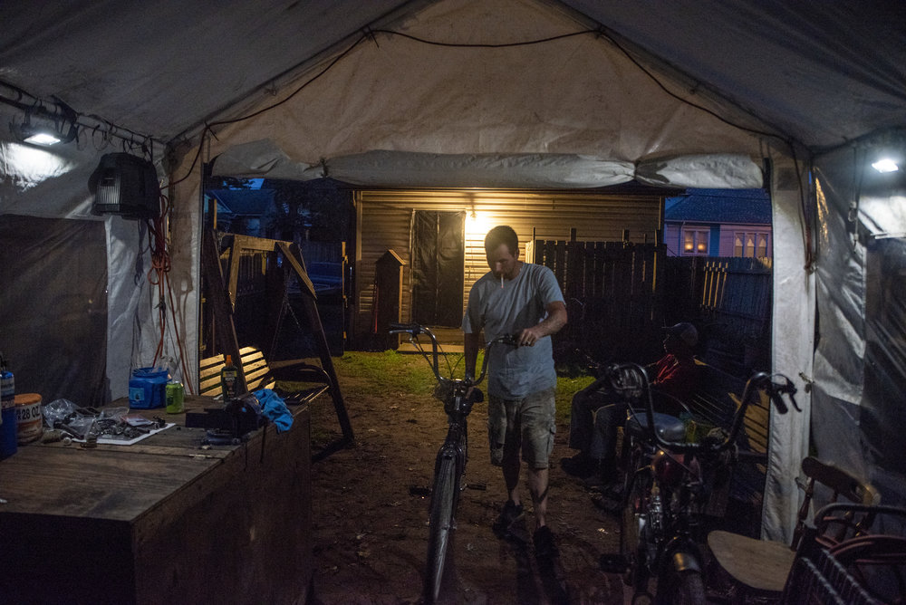 Calvin returns one of the motorized bicycles he was repairing that day to rest in the tent where he stores the rest of his clients' bicycles.