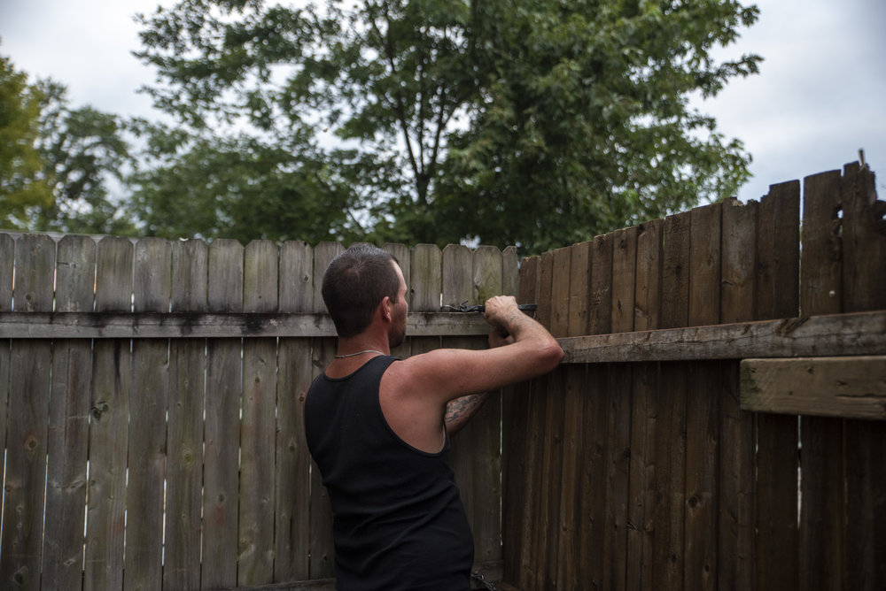 Calvin locks the fence to his backyard each night as he prepares to close up his motorized bicycle shop.