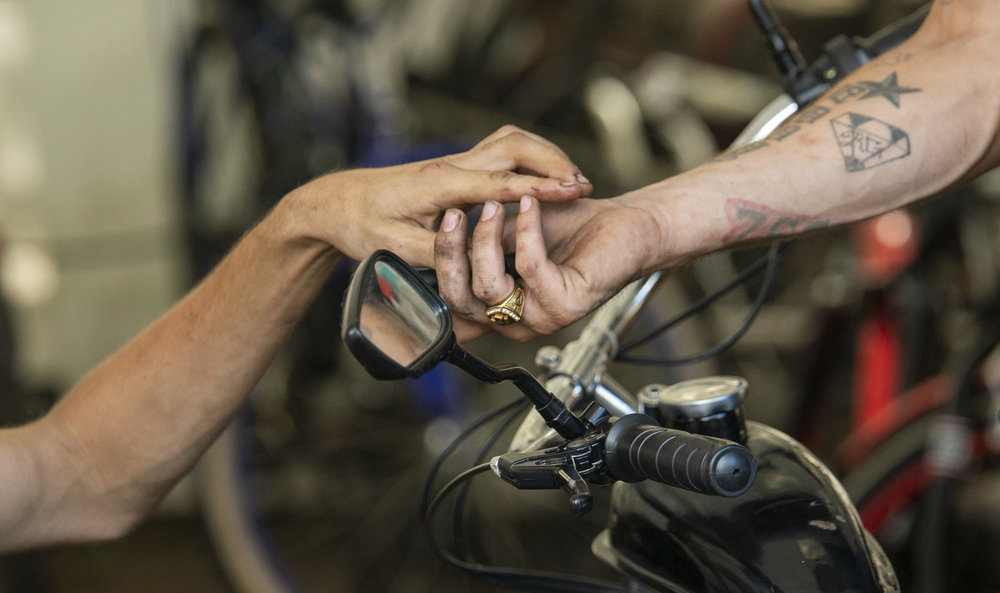 Dale Akers hands Dave a specific piece he needed to continue repairing his motorized bicycle.