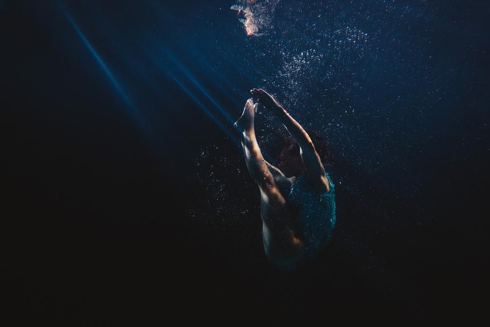 Blue light bounces of the figure of a dancer submerged underwater. ©- Matt Porteous
