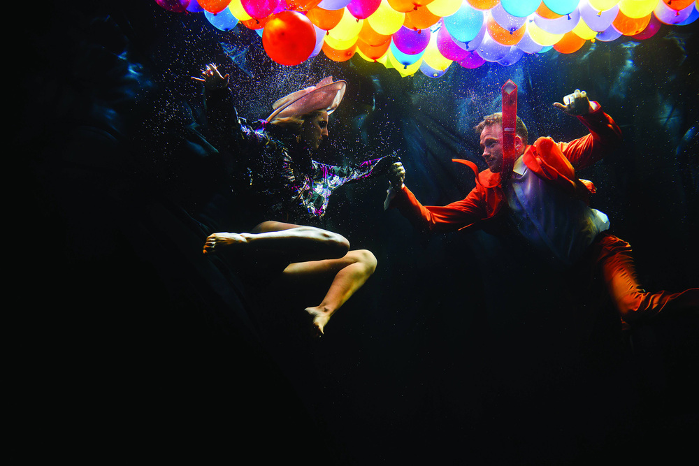 Vibrant ballons float on the surface unveiling a dancer duo underwater as they float gracefully through the water. ©- Matt Porteous