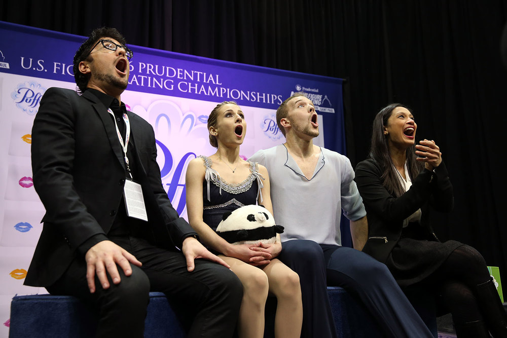 Skaters Tarah Kayne (with stuffed animal) and Daniel O'Shea and their coaches Jim Peterson (far left) and Amanda Evora, react with shock and delight over their personal-best score in the pairs free skate.  (U.S. Figure Skating / Jay Adeff)