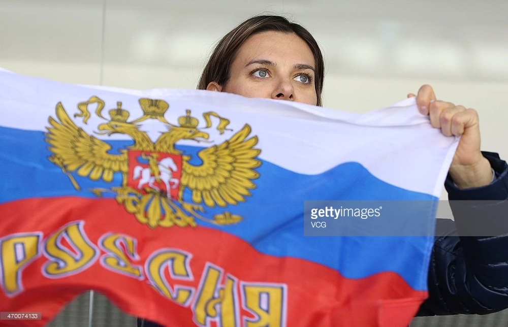 Yelena Isinbayeva with a Russian flag at a hockey game during the 2014 Winter Olympics in Sochi, Russia.  The two-time Olympic pole vault champion calls the ban on Russian track and field athletes a human rights violation.  (Getty Images)