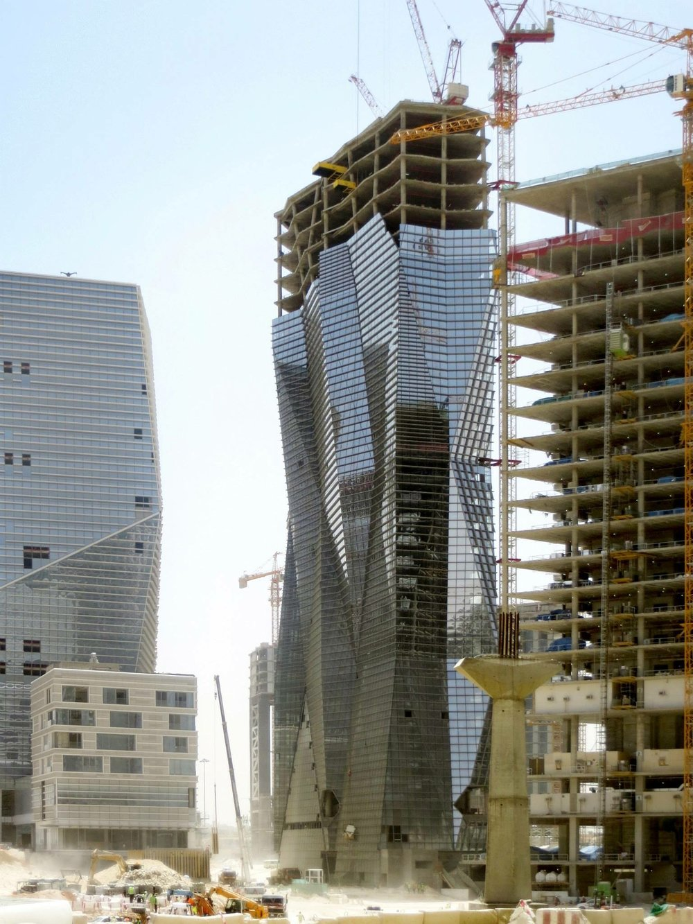 At right: the Muqarnas Tower under construction in King Abdullah financial district in Riyadh, Saudi, Arabia. Wong was the building's design architect (Jackie Wong photo)