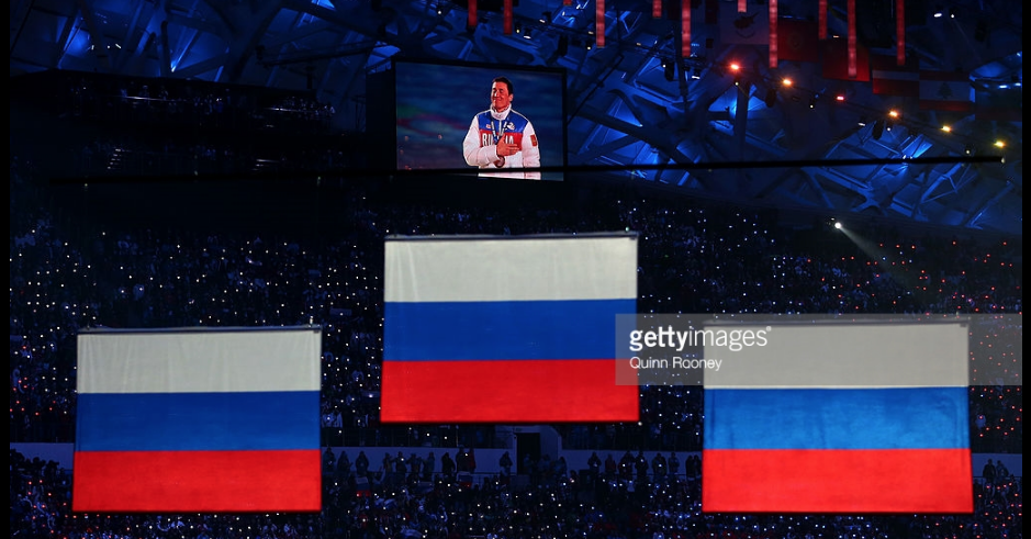 Gold medalist Alexander Legkov shown on the video screen as Russian flags are raised to mark its medal sweep in the 50-kilometer mass start cross-country ski race at the 2014 Olympics.  Legkov and silver medalist Maksim Vylegzhanin have been disqualified from those Games for doping, among the cases that led IOC to say no Russian flags will fly officially at 2018 Winter Games.