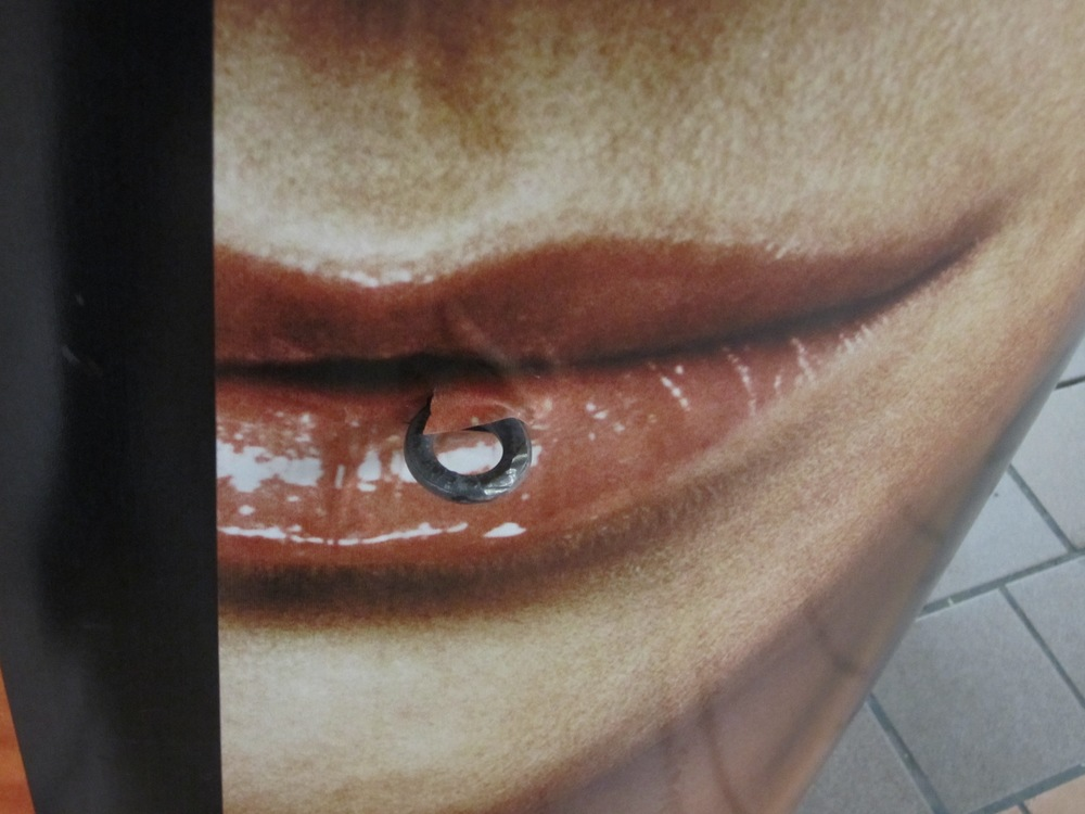"Advertisement wrapped around a column in the subway station at Grand Central. Purposeful or accidental relationship to existing eye-bolt? I call this ""lip ring"""