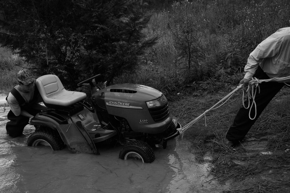 Sep. 29th, 2015 - Roger Polidoro (right) assists neighbour Dylan Harrell (left) in extracting the family lawn tractor from the rapidly rising waters. Harrell had already dragged the machine about 70 yards by the time he had reached shore.