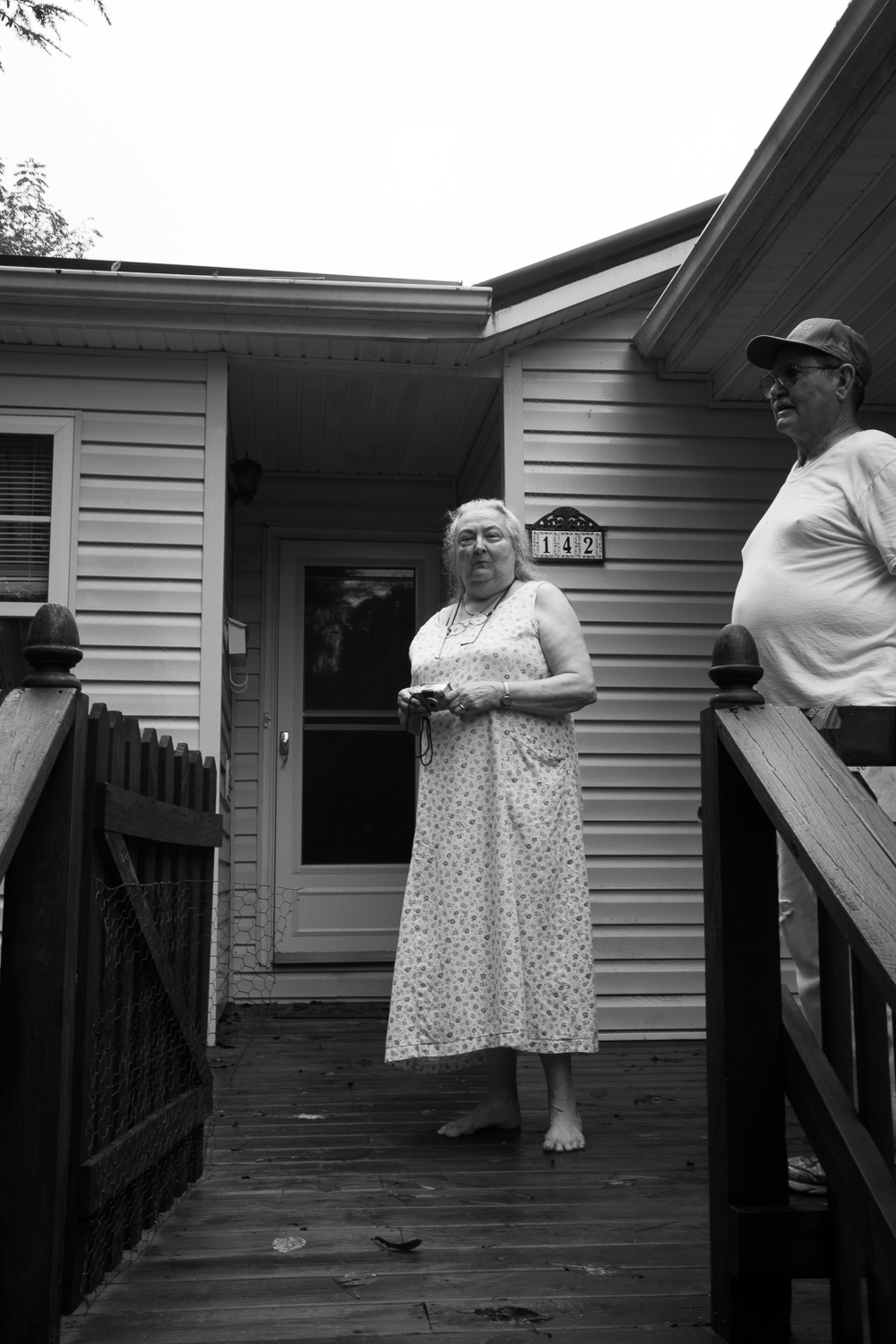 Sep. 29th, 2015 - After a late lunch, Jean Fletcher (centre) and her husband Franklin Fletcher Sr. (right) stand out on their porch, take pictures, and watch the rapidly rising water draw closer to their door.