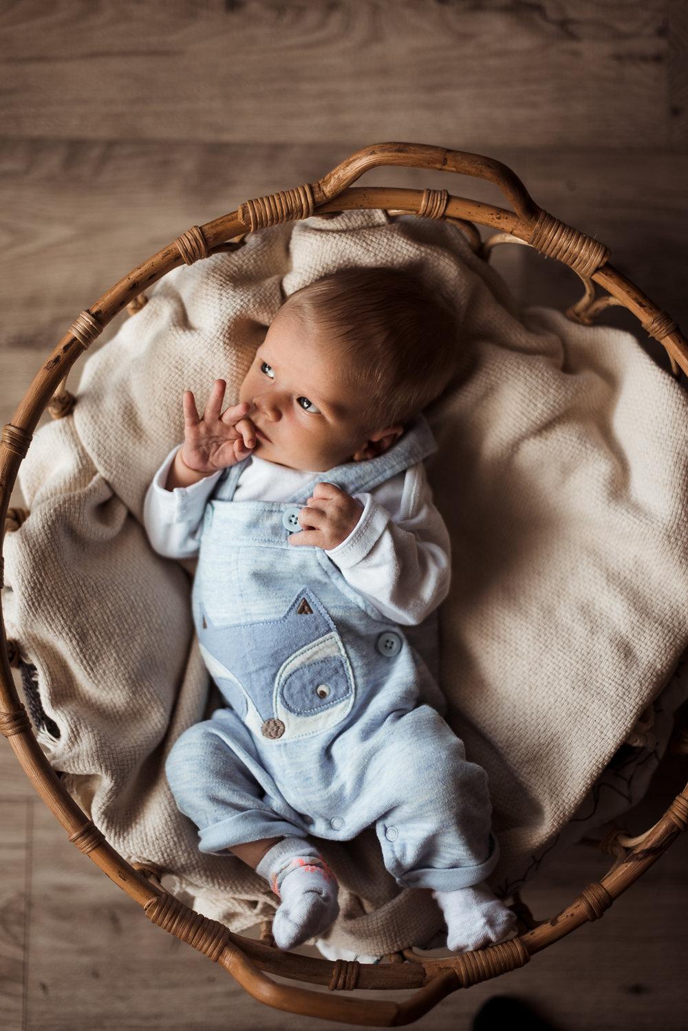 Toto bábätko je fotené v košíku vedľa veľkého okna. Bočné svetlo a tiene dodávajú fotke potrebnú hĺbku.