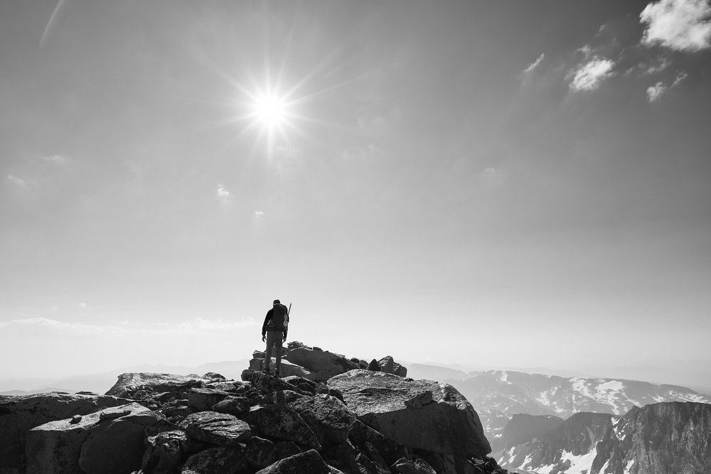 Adventure photography of a climber on the summit of Granite Peak, Montana