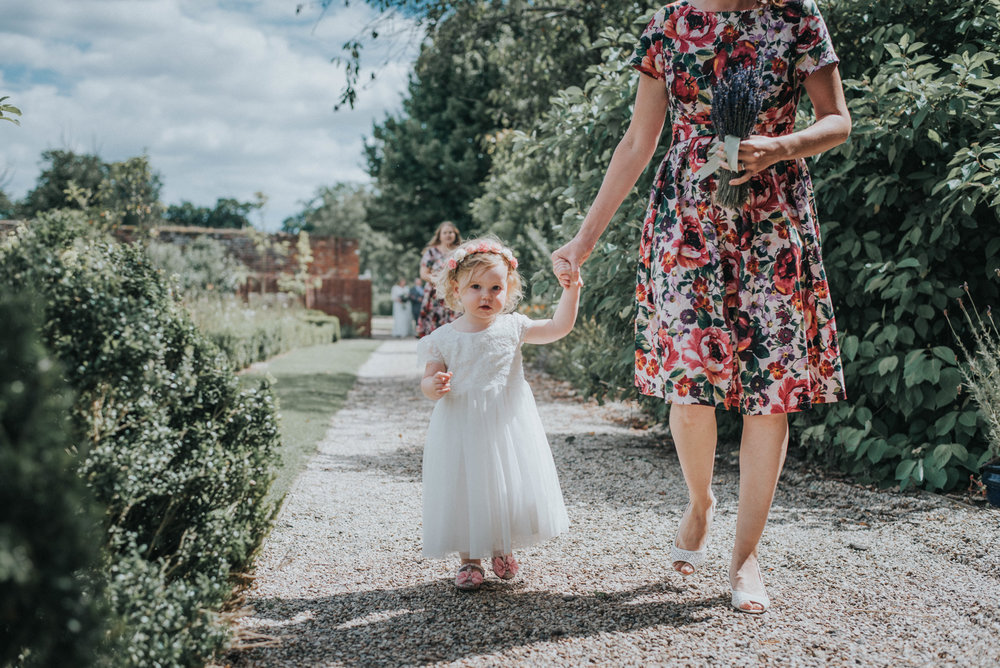 Flower girl and bridesmaid enter the ceremony Laura and Helgi Intimate secret garden Kent wedding