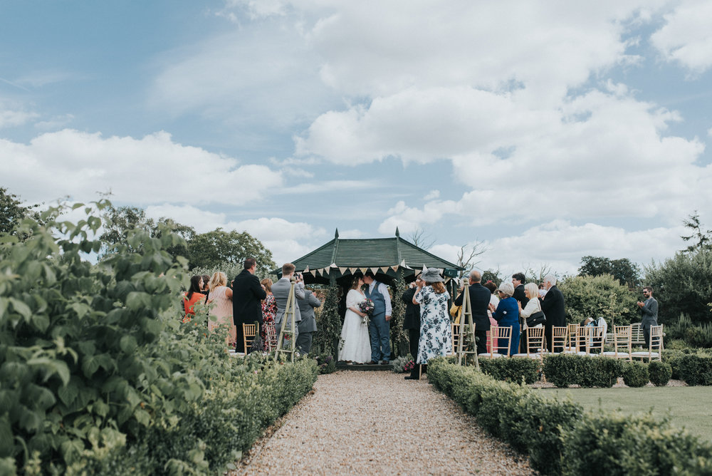 Bride and grooms First kiss Laura and Helgi Intimate secret garden Kent wedding