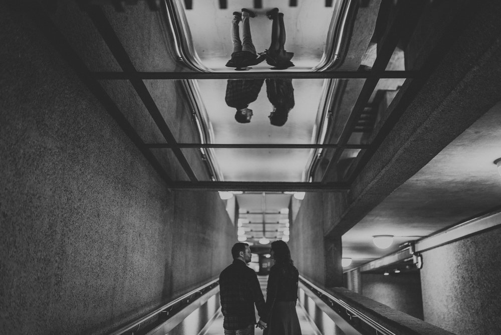 A quirky couple walking around the barbican centre holding hands using reflections