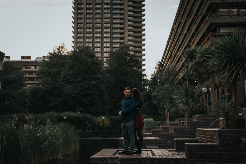 Couple closely hugging at the barbican centre whilst on their engagement shoot