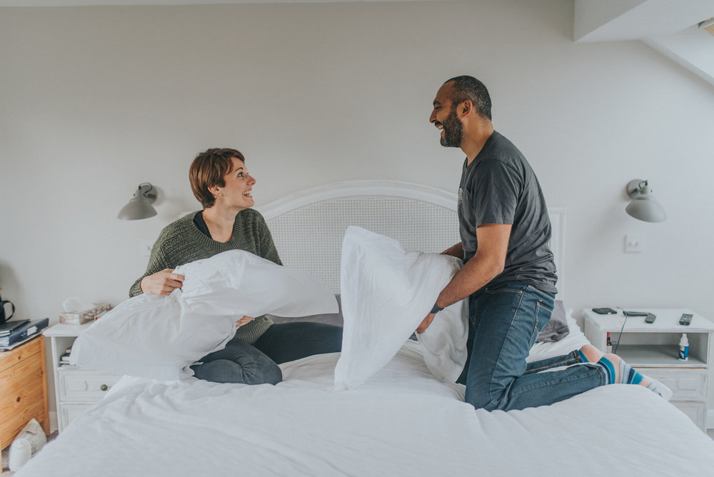 Couple having a pillow fight on their engagement shoot