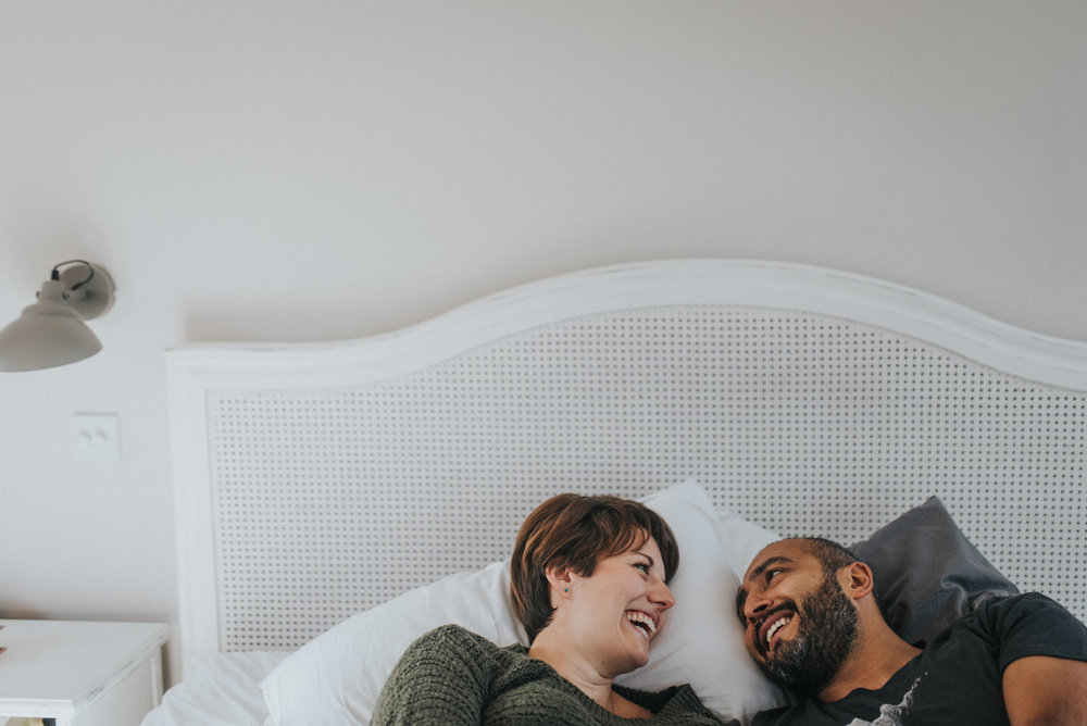 Couple in bed on their engagement shoot having a laugh