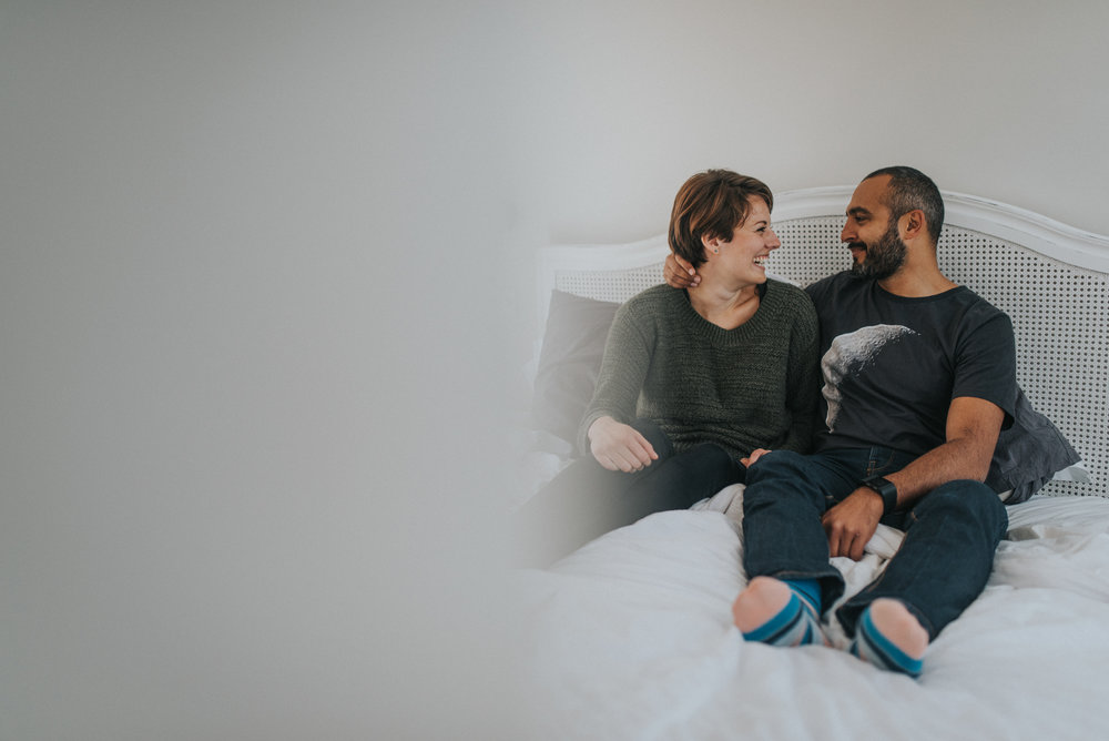 couple laying bed laughing