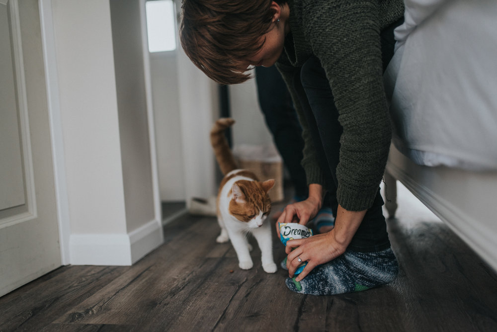 Couple feeding their cat during engagement shoot