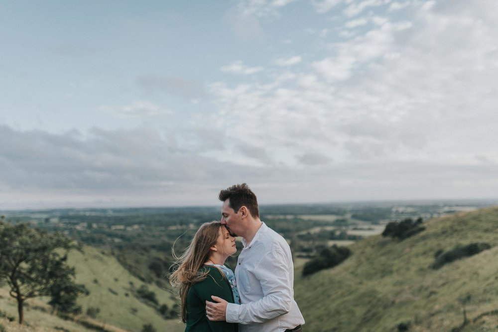 Windswept couple kissing | Romantic Kent Downs Engagement Photography wwww.baiandelle.com