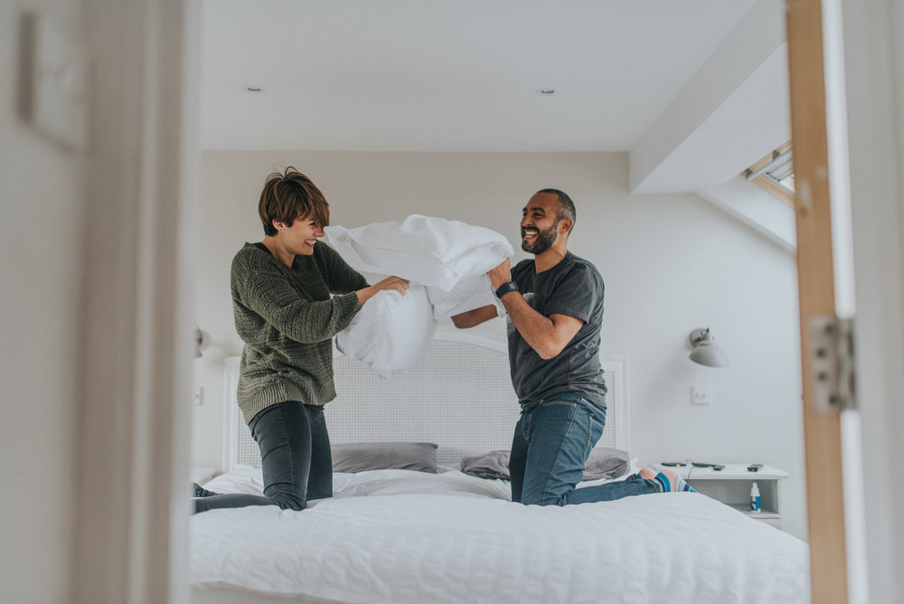 Couple having a pillow fight during their London home engagement shoot