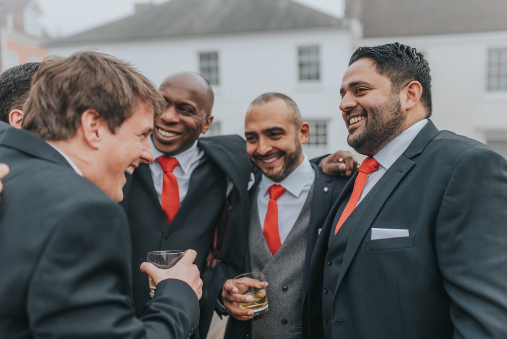 Groomsmen hugging at an Upwaltham barns Winter Wedding in Sussex