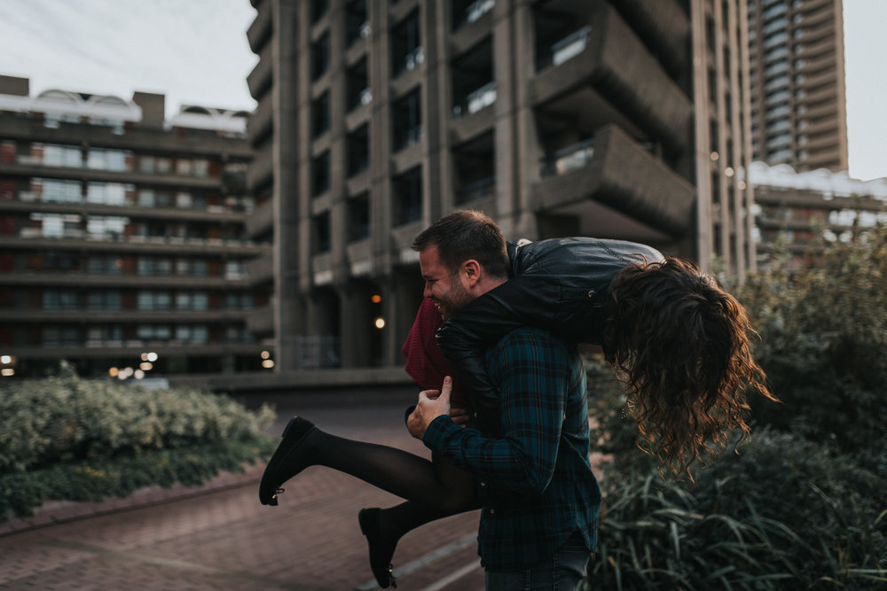 Girl being playfully lifted by her fiance during their fun Barbican Centre Engagement Shoot.