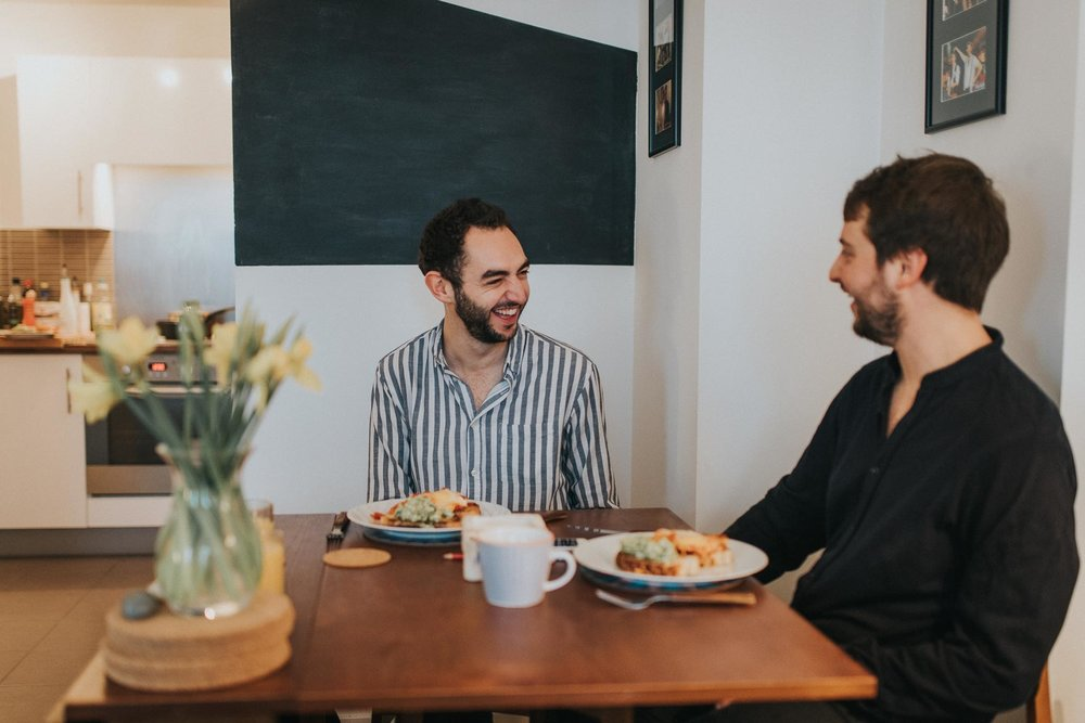couple laughing and having breakfast during their cosy at home london engagement shoot