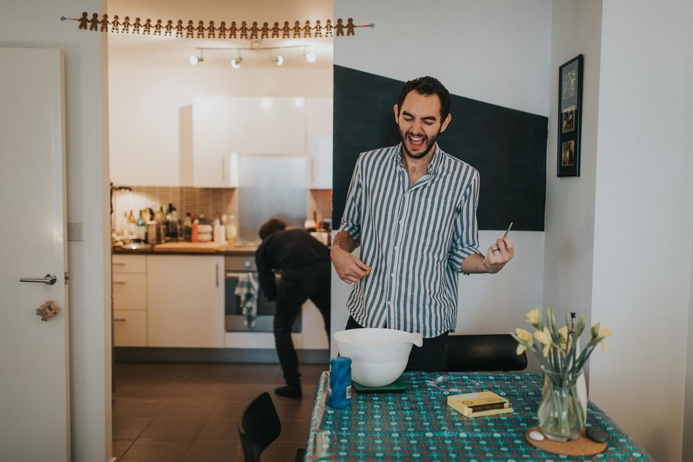 fun couple baking and singing along to the radio during their cosy at home london engagement shoot