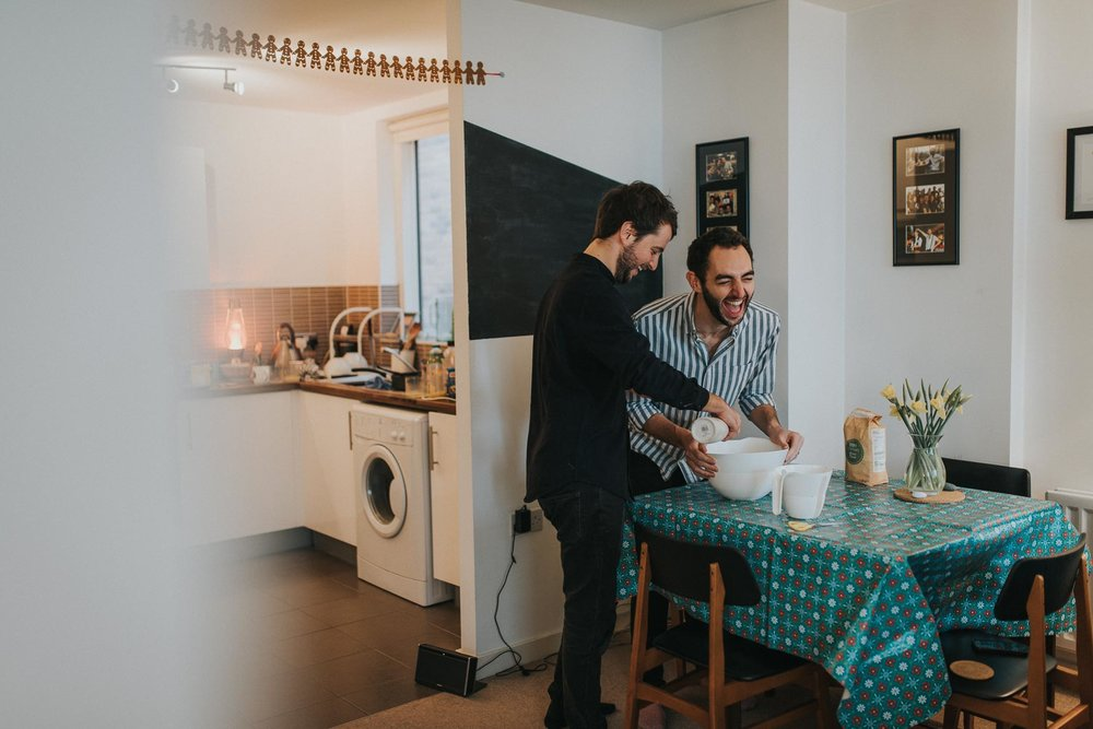 fun couple laughing and baking during their cosy at home london engagement shoot
