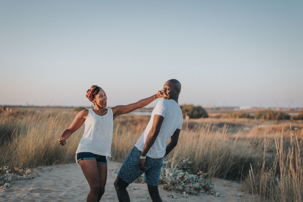 Fun couple play fighting on a beach in Spain | Destination engagement photography www.baiandelle.com