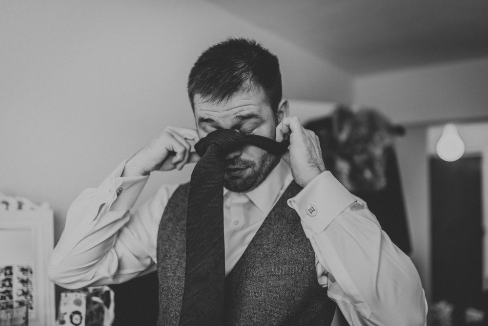 Groom putting on his tie | Creative, fun and romantic Hertfordshire wedding photography  www.baiandelle.com