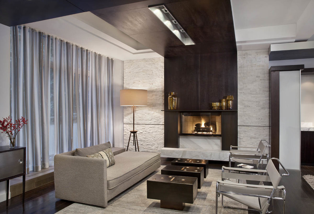 A seating area with a finished fireplace meets guests upon entry. A modern and inviting parlor.
