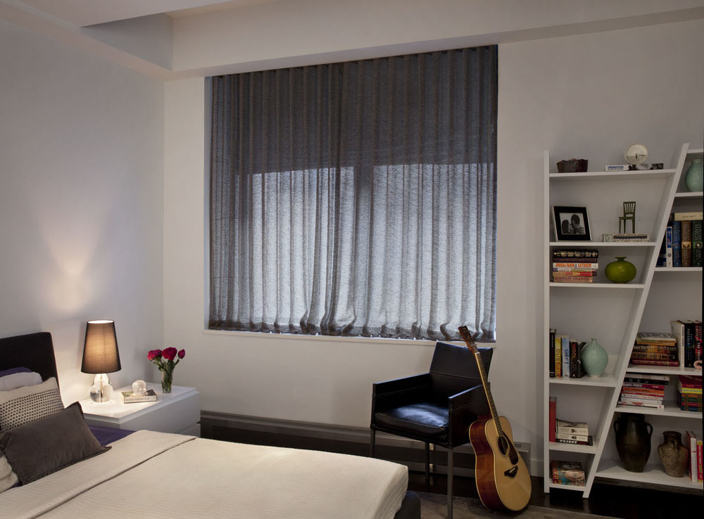 Custom, double layered window treatments soften the master bedroom and new, clean-lined storage and lighting.