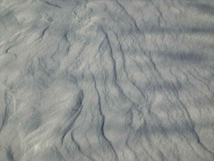 Wind lines on a snowy hillside
