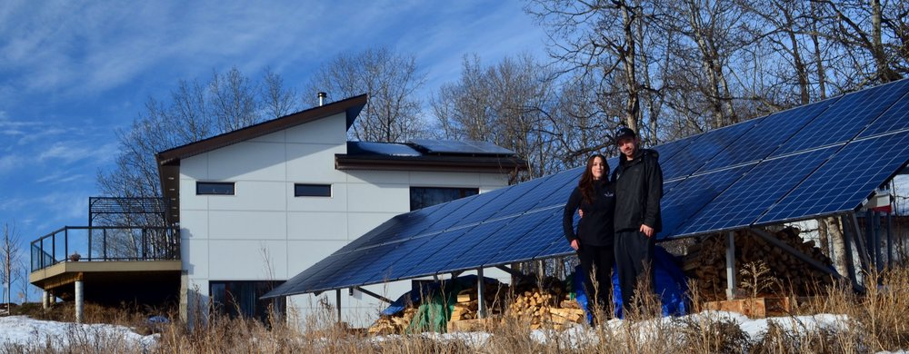 """Standing in front of the ground-mount """"off-grid"""" portion of our solar system. You can see the wood stored underneath, as the panels provide a dual purpose!"""