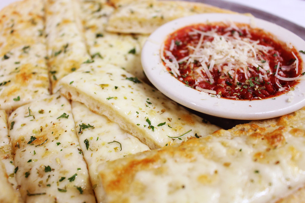 Focaccia - Our rustic appetizer is a thick slab of focaccia bread slathered in Italian cheeses and/or an herb medley, cut and served with hot marinara for dipping.with Herbs - $6.95with Cheese - $7.95