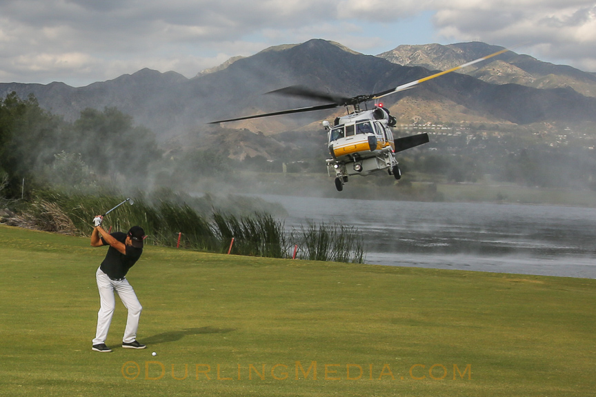 "An LACoFD Firehawk returns to the fire after filling up at a nearby golf course while a golfer ""plays through""."
