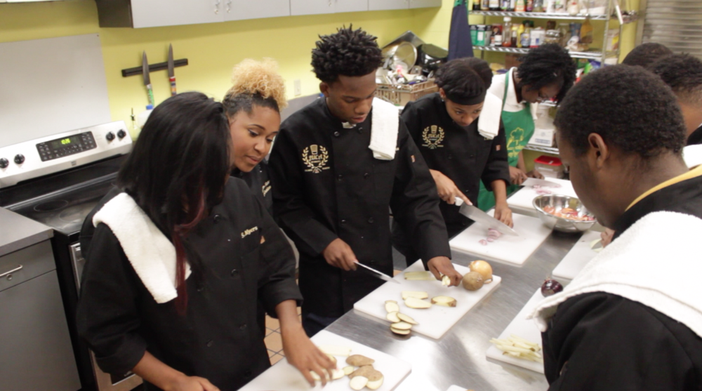 Chef Aryen Moore-Alston, Chef-in-Residence at the Jay Uiberall Culinary Academy at Knowledge Quest, giving instruction.
