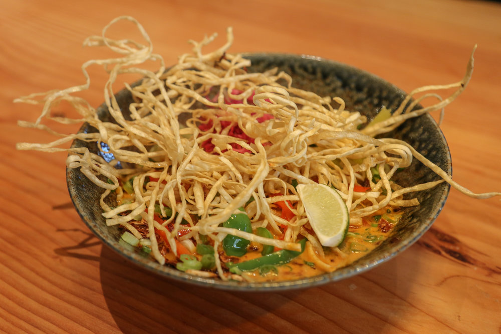 Thaitanium- thai style khao soi with steamed and crispy egg noodles thai red and yellow curry, organic peppers, and traditional accompinaments
